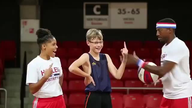 Members of the Harlem Globetrotters show a kid how easy it is to spin a basketball on your finger