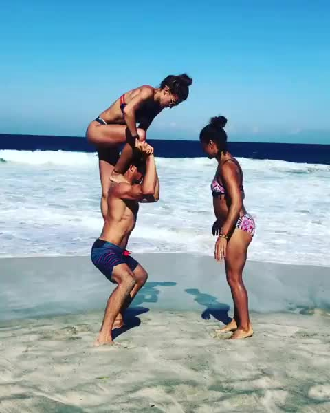 amazing, beach, beautiful, man, move, strength, strong, three, trick, wtf, Nicholas Coolridge supporting two women, one on his shoulder and the other using his and the other women's hands. GIFs