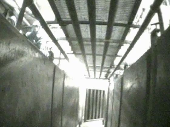 Kameran går genom en trång gång med gallertak