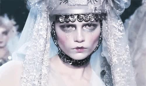 Russian ice queen Natasha Poly wears a silver embroidered lace veil along with a glittery coin armour headpiece at one of the best runway sh