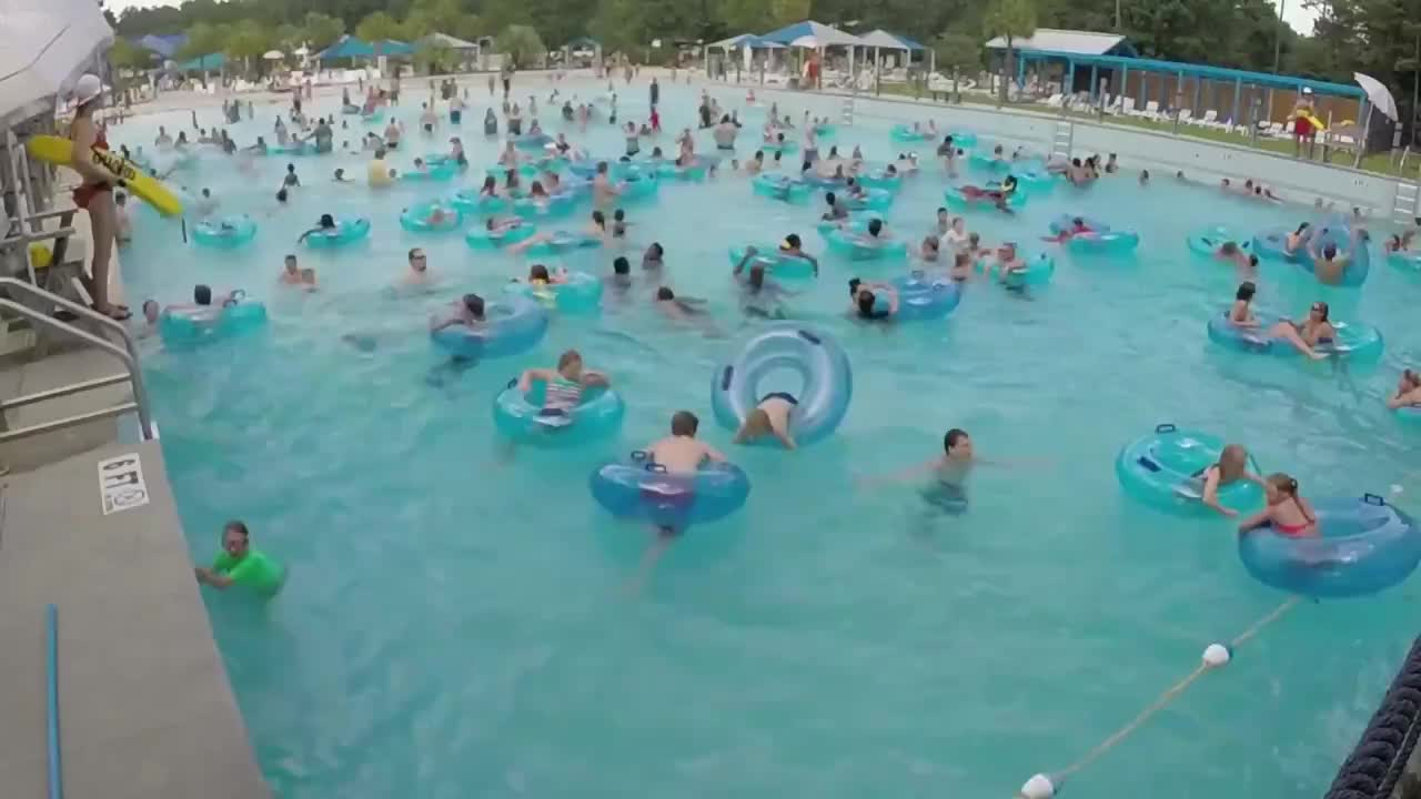 Alert lifeguard spotting a kid drowning in a crowded wave pool GIFs