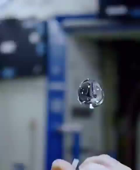 Astronaut coloring an orb of water with different dyes as it floats around in zero gravity GIFs