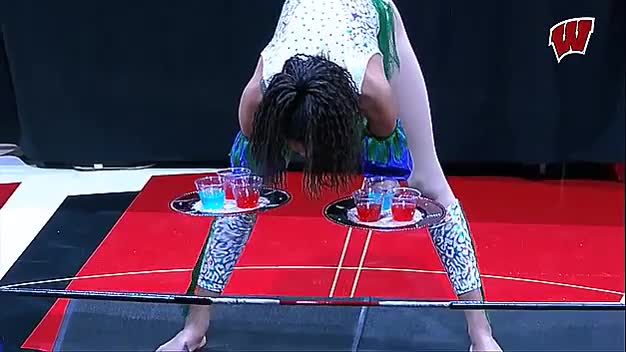 Professional limbo performer Shemika Charles performing a 10 inch limbo with two trays of drinks at a Wisconsin half time show GIFs