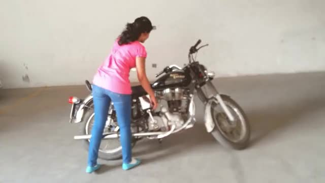 Girl hand starting Royal enfield Bullet
